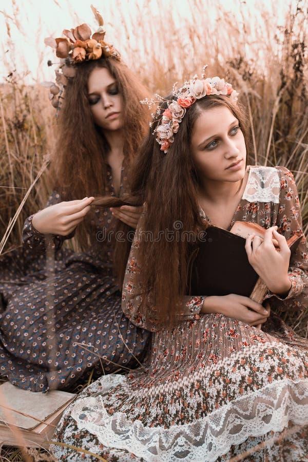 Forme el retrato de dos muchachas hermosas en la ropa diseñada boho que lleva del campo de la puesta del sol imágenes de archivo libres de regalías