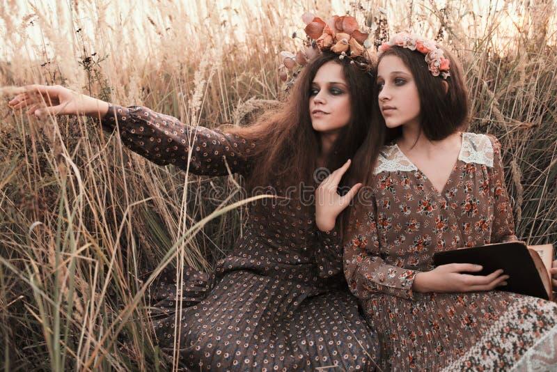 Forme el retrato de dos muchachas hermosas en la ropa diseñada boho que lleva del campo de la puesta del sol imagen de archivo