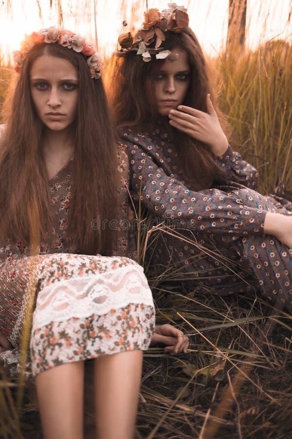 Forme el retrato de dos muchachas hermosas en la ropa diseñada boho que lleva del campo de la puesta del sol imagenes de archivo