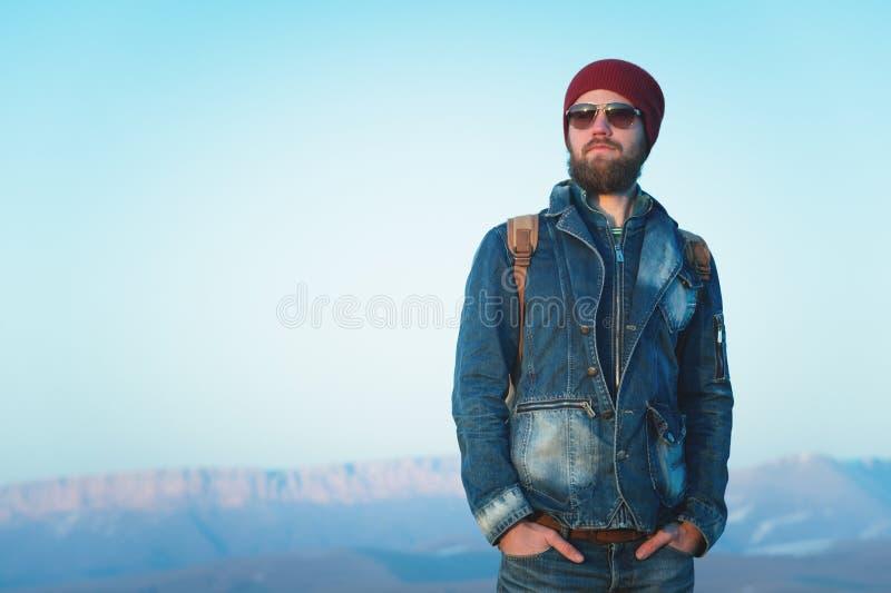Forme el retrato de gafas de sol que llevan barbudas de un hombre joven del inconformista, de una mochila y del sombrero en un fo imagenes de archivo