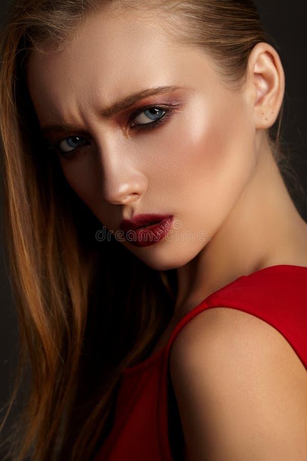 Forme el retrato de la muchacha atractiva joven en vestido rojo imagenes de archivo