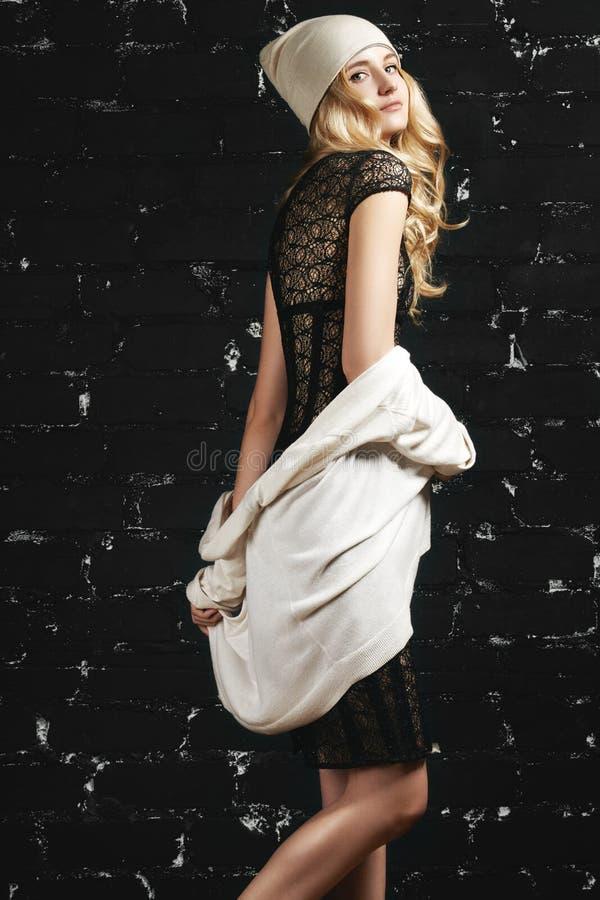 Forme el retrato de la muchacha de moda con el pelo rubio, llevando un vestido y una chaqueta negros que se oponen a la pared urb fotos de archivo libres de regalías