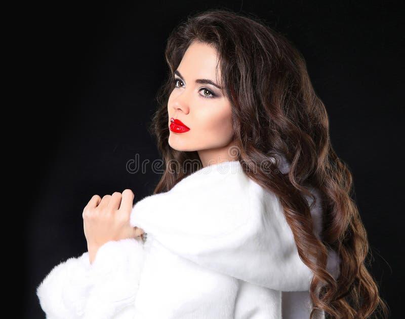 Forme el retrato de la muchacha morena hermosa en el abrigo de pieles blanco A imagen de archivo