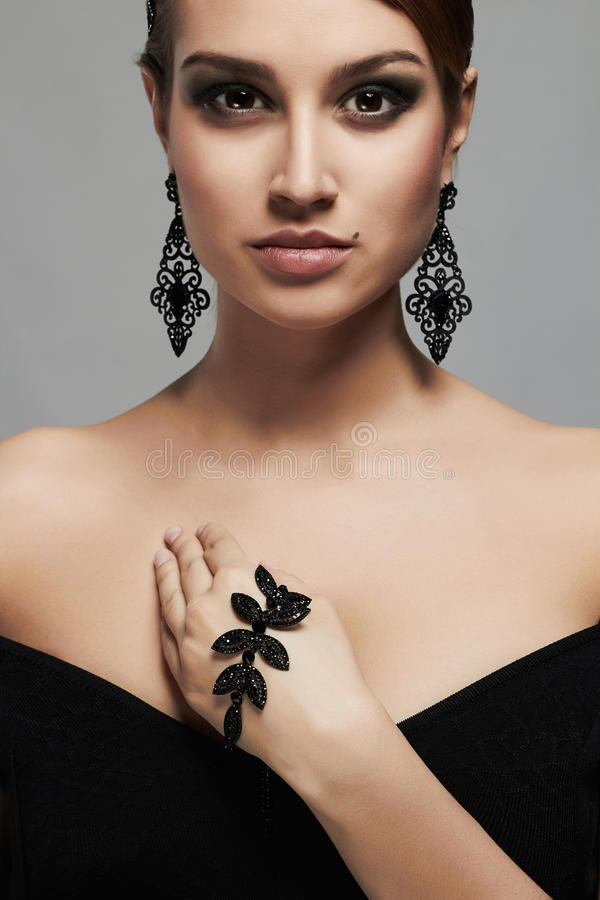 Forme el retrato de la mujer atractiva hermosa joven en joyería Señora elegante en alineada negra imagen de archivo