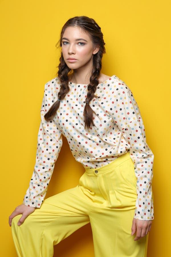 Forme el retrato de la mujer elegante joven en estudio Backgr amarillo fotos de archivo libres de regalías