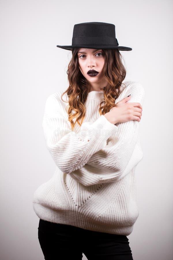Forme el retrato de la mujer morena del encanto hermoso en el suéter blanco y el sombrero negro en el fondo blanco mirada de la c fotos de archivo