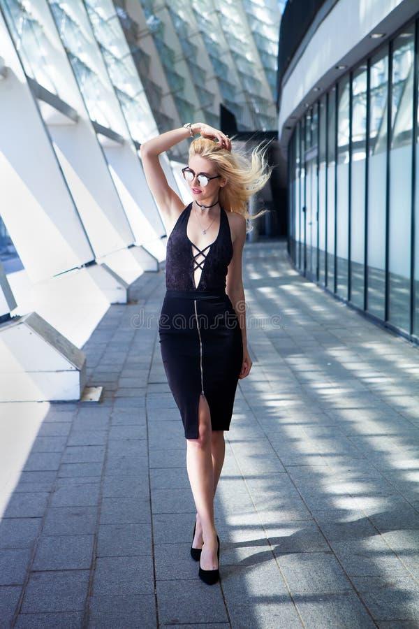 Forme el retrato de la mujer rubia elegante joven al aire libre las gafas de sol, el ahogador, la falda negra y el negro sexy rem imagenes de archivo