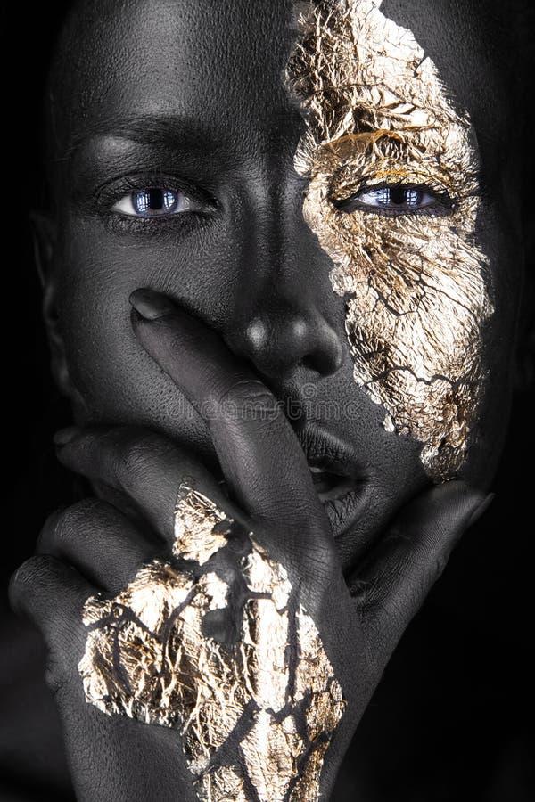 Forme el retrato de una muchacha de piel morena con oro imagen de archivo libre de regalías