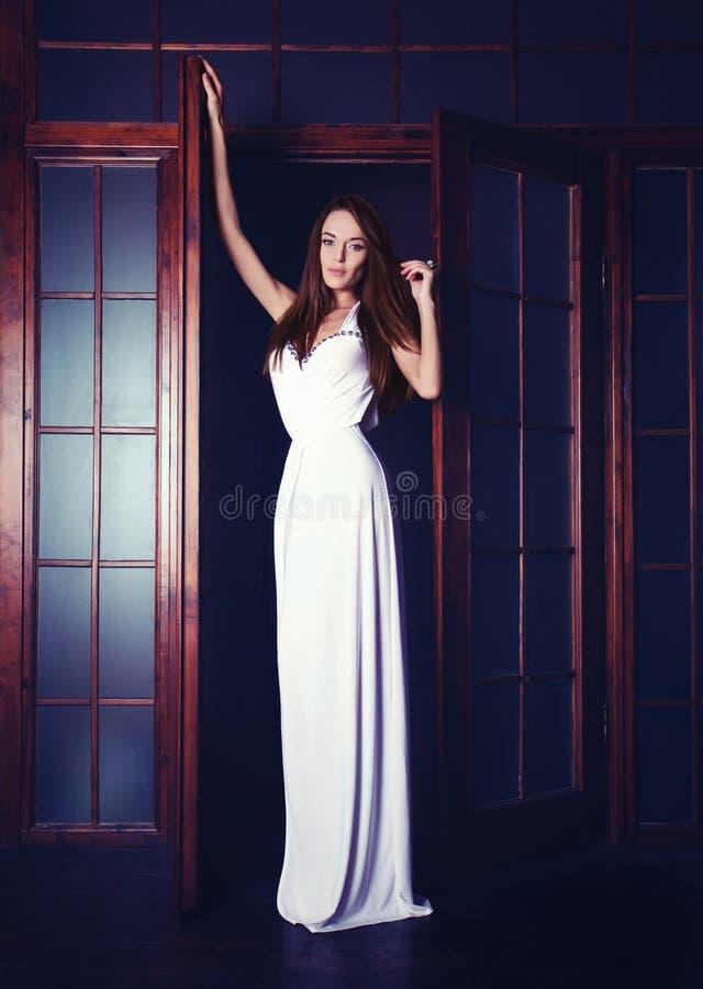 Forme el retrato de una muchacha que lleva un vestido blanco largo foto de archivo libre de regalías