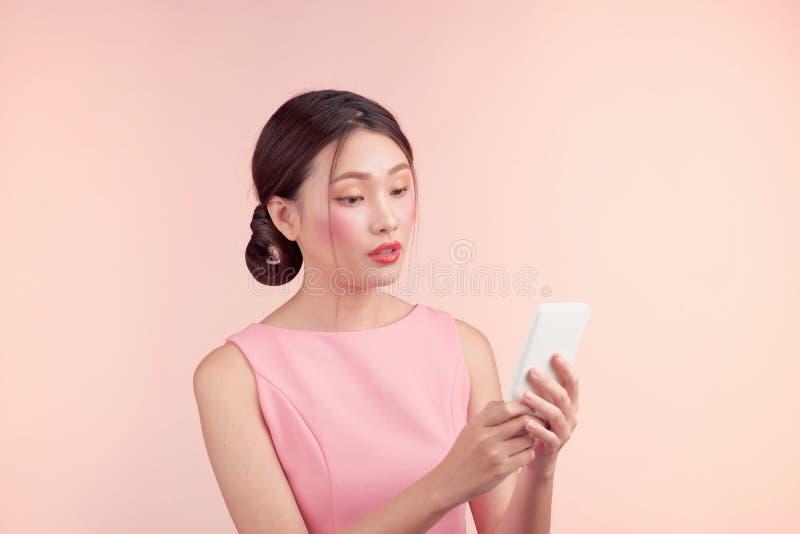 Forme el retrato de una mujer joven hermosa en un vestido bonito sobre fondo rosado fotos de archivo