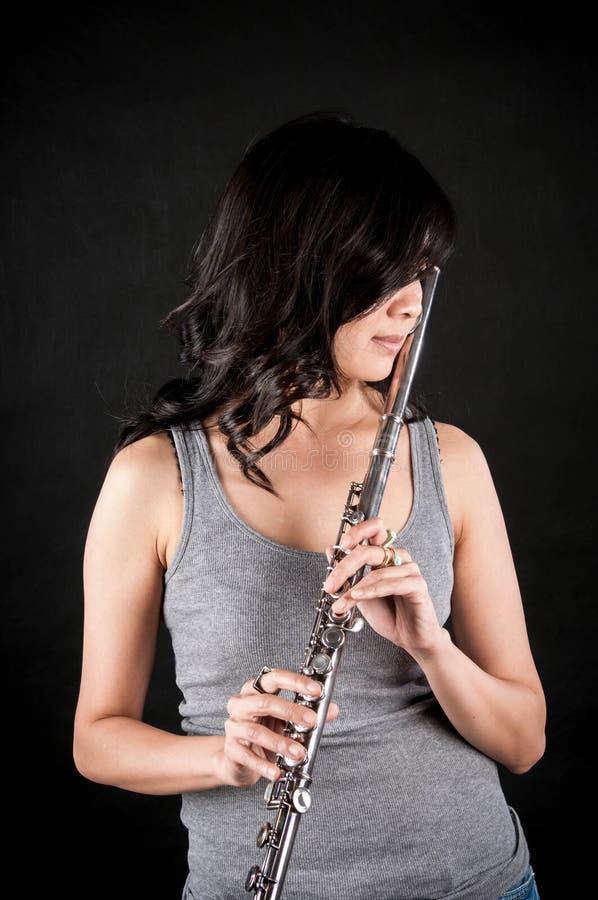 Forme el retrato en estudio de la mujer joven hermosa que siente feliz con su flauta contra fondo oscuro en estudio imagen de archivo libre de regalías