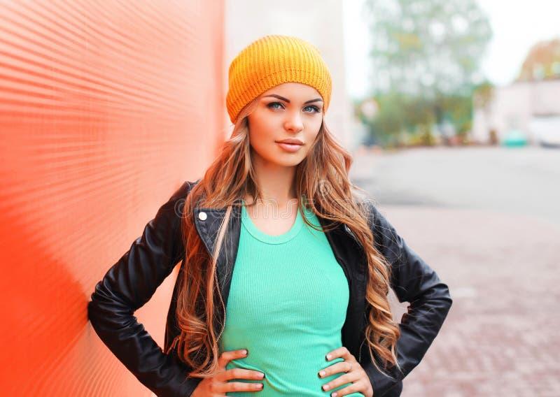 Forme el sombrero de la chaqueta de la mujer que lleva bastante joven sobre rojo colorido imágenes de archivo libres de regalías