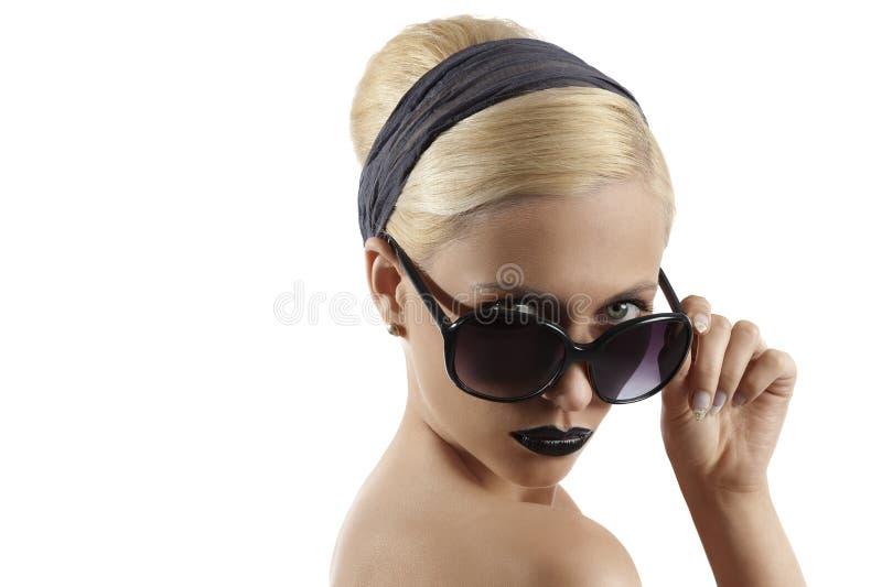 Forme el tiro de la muchacha rubia con la presentación de las gafas de sol foto de archivo