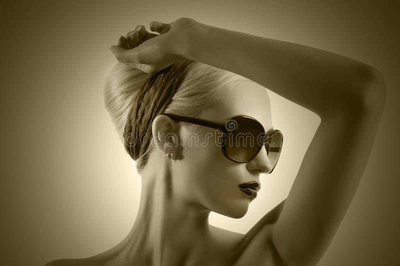 Forme el tiro de la muchacha rubia con la presentación de las gafas de sol fotos de archivo libres de regalías