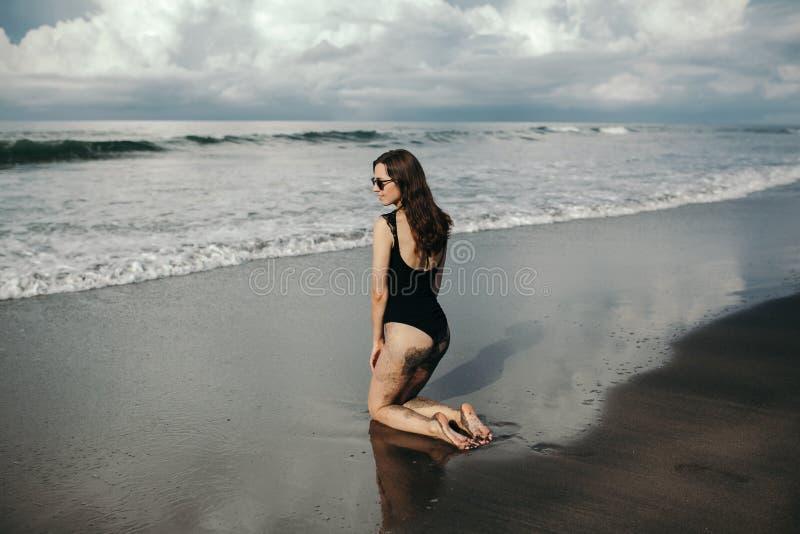 Forme el tiro de la vista posterior de la muchacha hermosa con extremo arenoso en traje de baño negro y las gafas de sol que pres fotografía de archivo libre de regalías