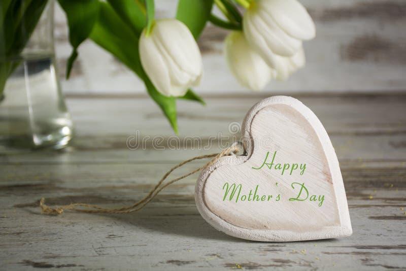 Forme en bois de coeur devant les tulipes blanches sur une étiquette rustique grise image libre de droits
