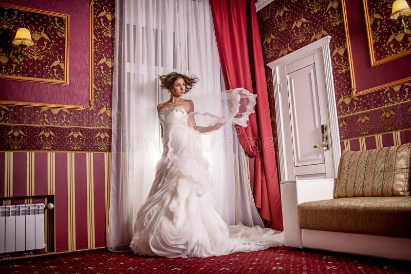 Forme a foto da moda a noiva bonita com cabelo encaracolado em um vestido de casamento lindo com poses perfeitas preciosas no int imagens de stock royalty free