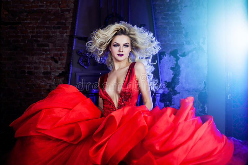 Forme a foto da mulher magnífica nova no vestido vermelho Retrato do estúdio imagem de stock royalty free