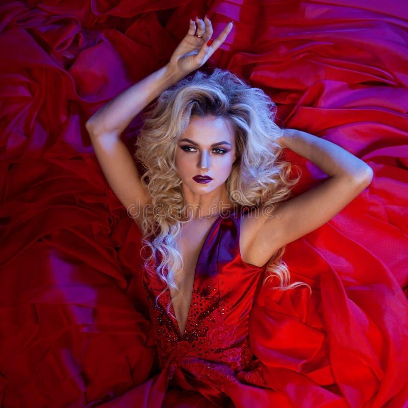Forme a foto da mulher magnífica nova no vestido vermelho Retrato do estúdio imagens de stock