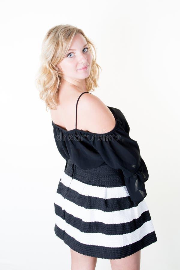 Forme a foto de uma mulher loura nova bonita em um levantamento preto do vestido bonito sobre o branco foto de stock