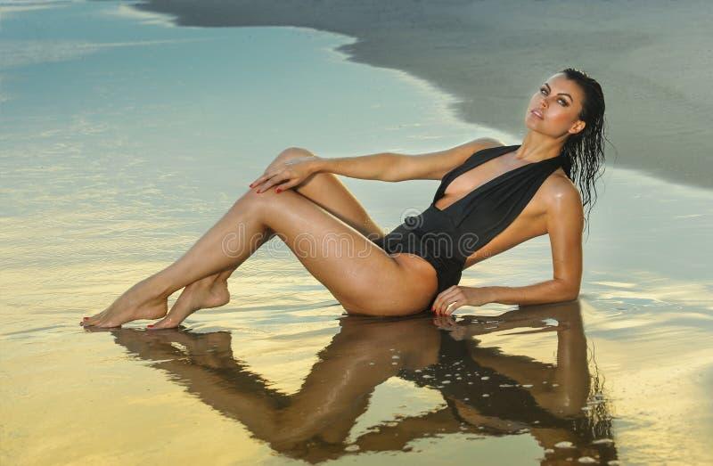 Forme a foto exterior da mulher moreno 'sexy' lindo no roupa de banho preto elegante que levanta na praia imagens de stock royalty free