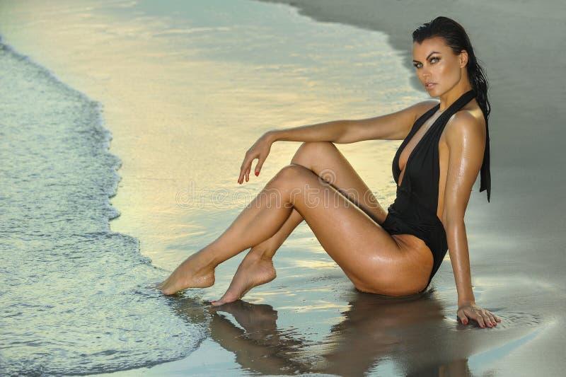 Forme a foto exterior da mulher moreno 'sexy' lindo no roupa de banho preto elegante que levanta na praia imagem de stock