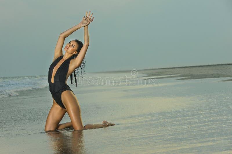 Forme a foto exterior da mulher moreno 'sexy' lindo no roupa de banho preto elegante que levanta na praia imagem de stock royalty free