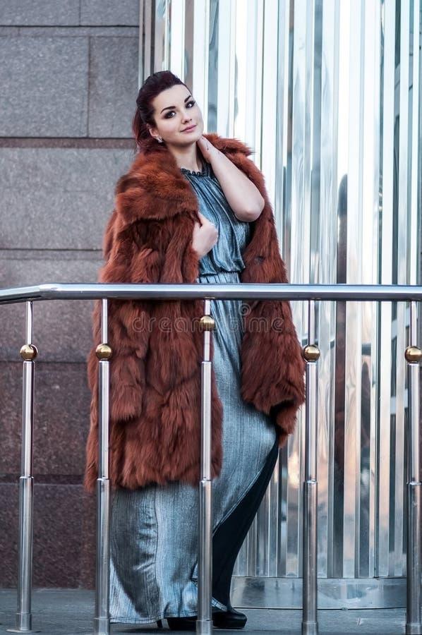 Forme a foto exterior da mulher 'sexy' do encanto com o cabelo escuro que veste o casaco de pele luxuoso e as luvas de couro, lev imagens de stock