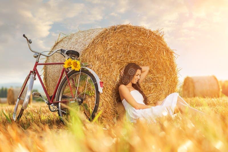 Forme a foto, mulher bonita que senta-se na frente dos pacotes do trigo, ao lado da bicicleta velha fotos de stock