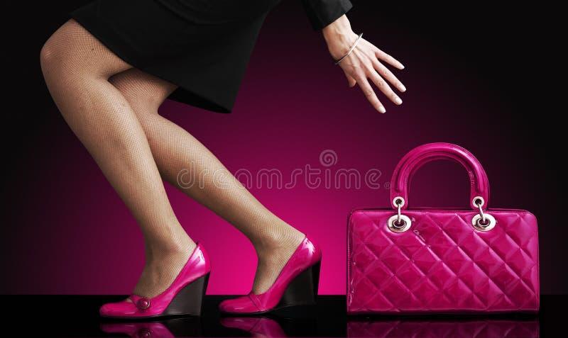 Forme a foto, pés 'sexy' da mulher com bolsa fotografia de stock royalty free