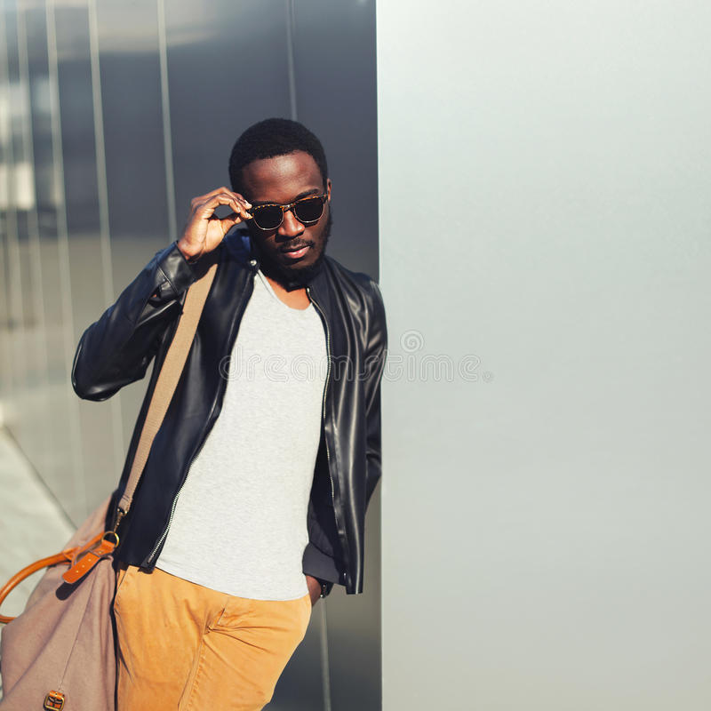 Forme a homem africano vestir de levantamento modelo óculos de sol e o casaco de cabedal preto da rocha com o saco na cidade, cop foto de stock royalty free