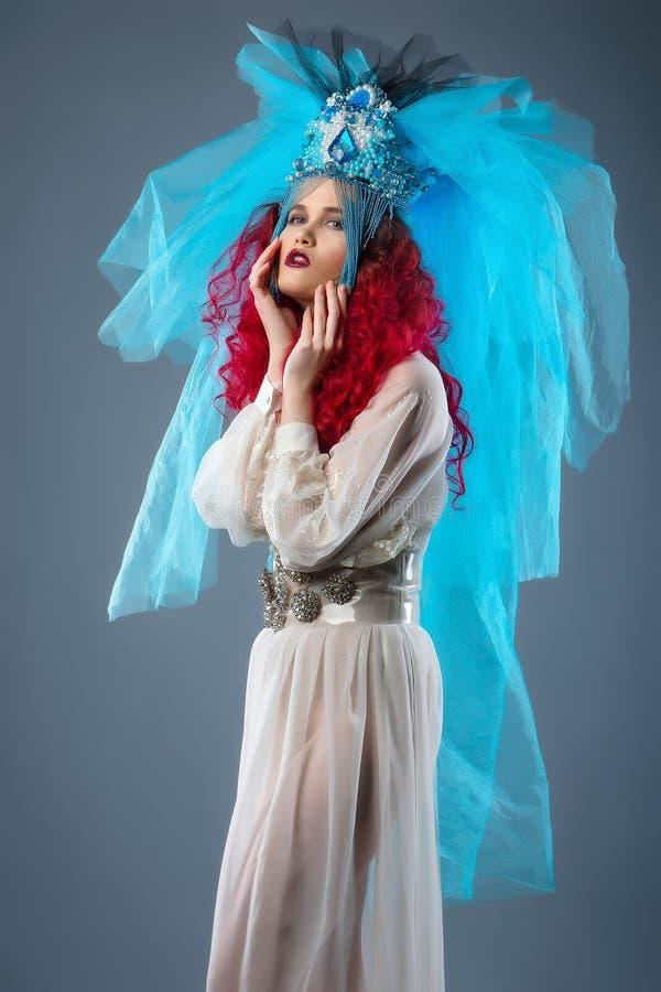 Forme increíblemente a la muchacha con el pelo rojo en corona y velo foto de archivo