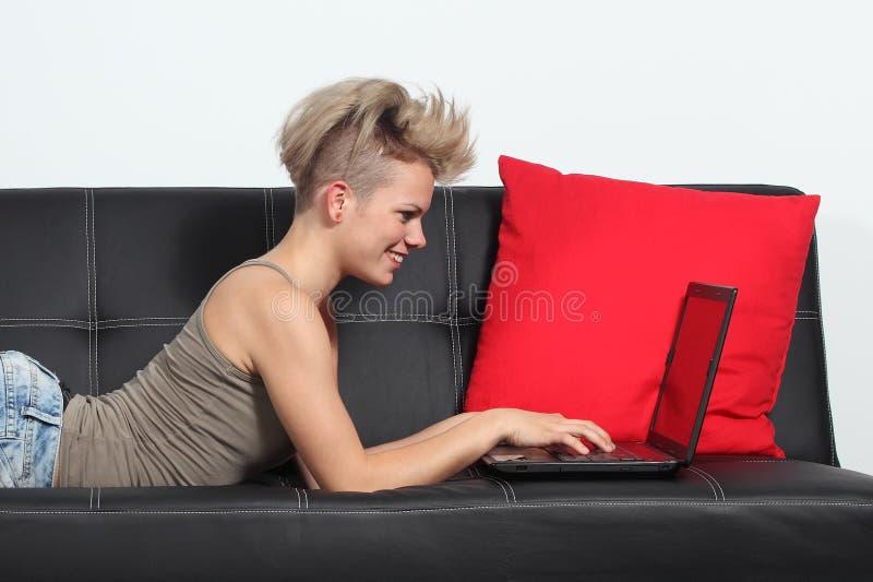 Forme Internet de la ojeada de la mujer en un ordenador portátil en casa fotos de archivo