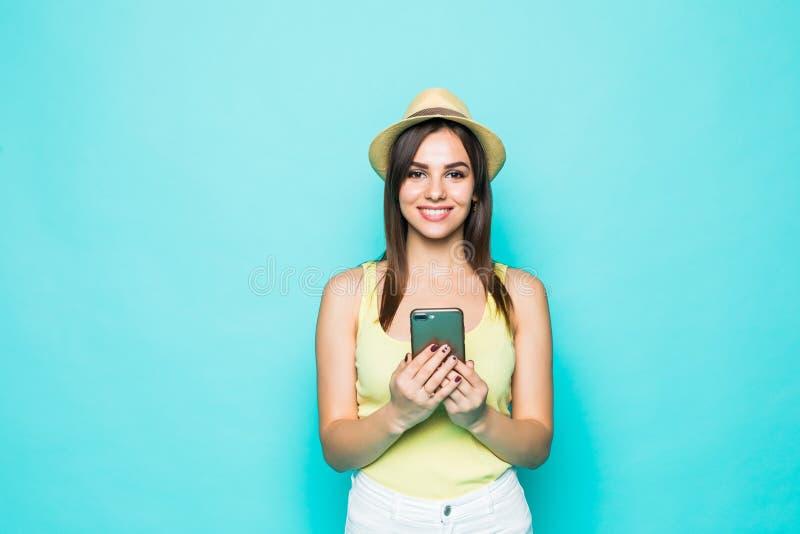 Forme a jovem mulher bonita o chapéu vestindo de utilização modelo do smartphone as calças brancas sobre o fundo verde colorido foto de stock royalty free