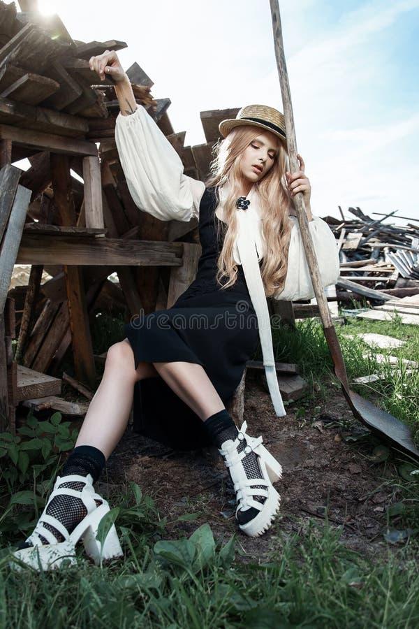 Forme a jovem mulher que veste o chapéu à moda do vestido e de palha no campo Estilo da forma de Amish fotos de stock