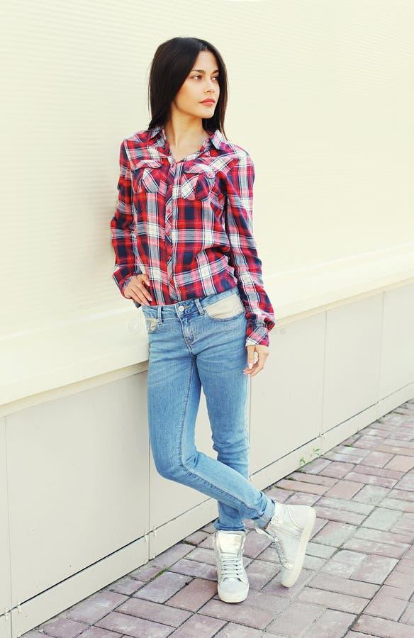 Forme a jovem mulher que veste uma camisa quadriculado e calças de brim na cidade fotos de stock