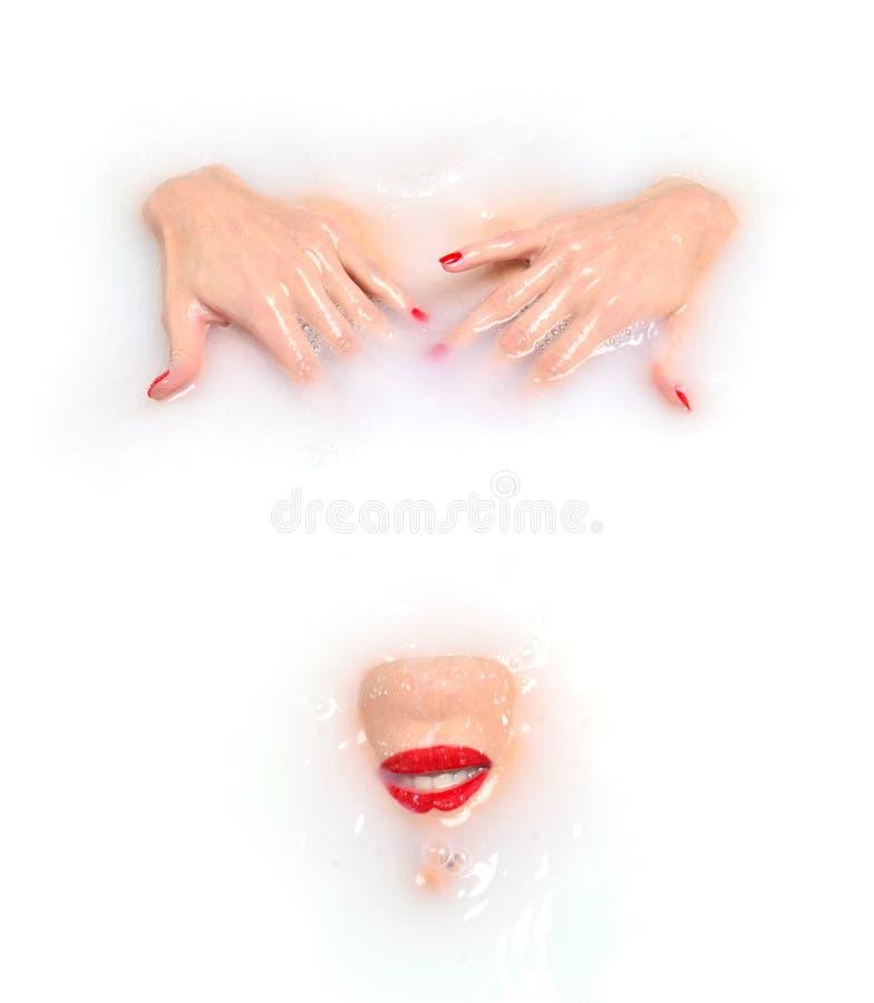 Forme la cara atractiva de la mujer con la mentira roja de los labios dibujada en la leche blanca fotografía de archivo