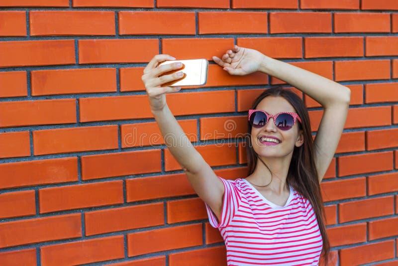 Forme a la chica joven bastante sonriente que toma el autorretrato de la imagen en smartphone en camiseta rayada sobre fondo del  imagen de archivo libre de regalías
