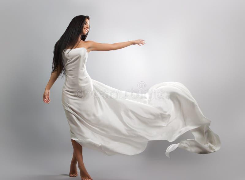 forme la foto de la chica joven en el tejido blanco del vuelo del vestido Material ligero imagen de archivo