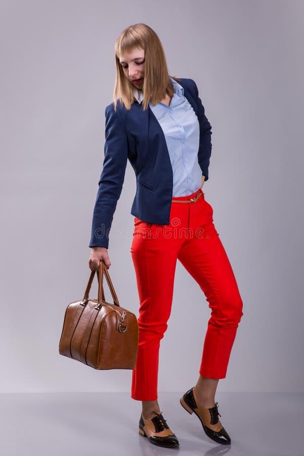 Forme la mirada de pantalones rojos vestidos mujer, chaqueta azul, bolso marrón el modelo mira un bolso de cuero altura completa fotos de archivo