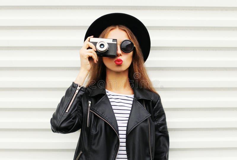Forme la mirada, modelo bastante fresco de la mujer joven con la cámara retra de la película que lleva el sombrero negro elegante foto de archivo