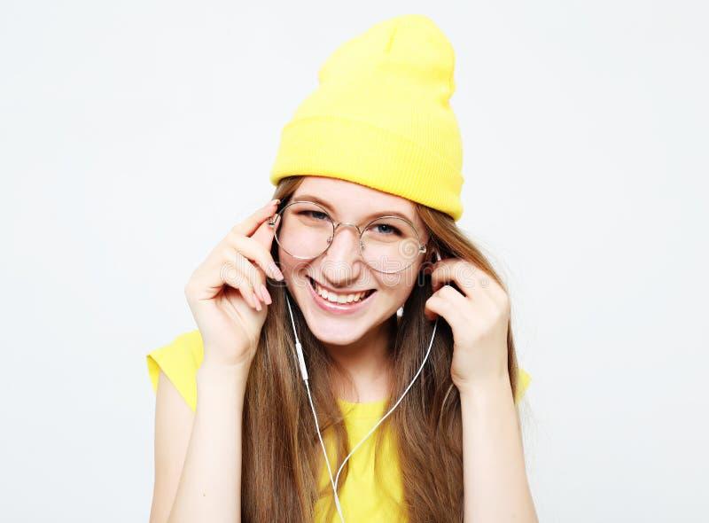 Forme a la muchacha bastante fresca en auriculares que escucha la música que lleva el sombrero y la camiseta amarillos foto de archivo libre de regalías