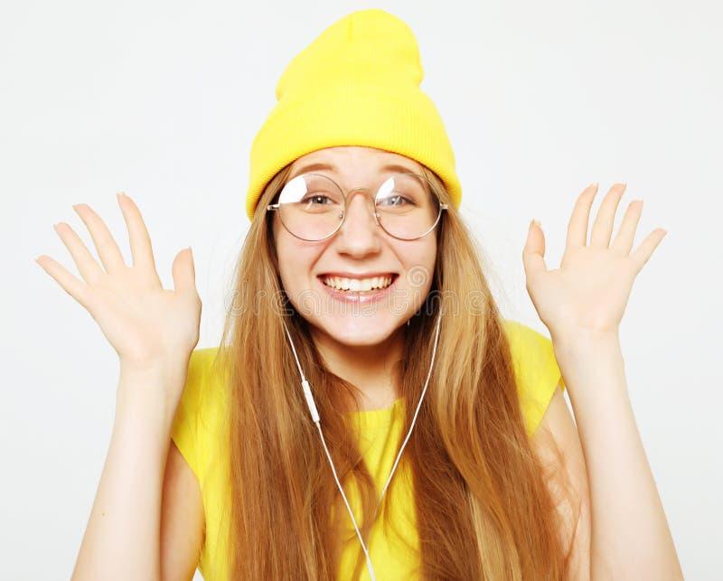 Forme a la muchacha bastante fresca en auriculares que escucha la música que lleva el sombrero y la camiseta amarillos sobre el f imágenes de archivo libres de regalías