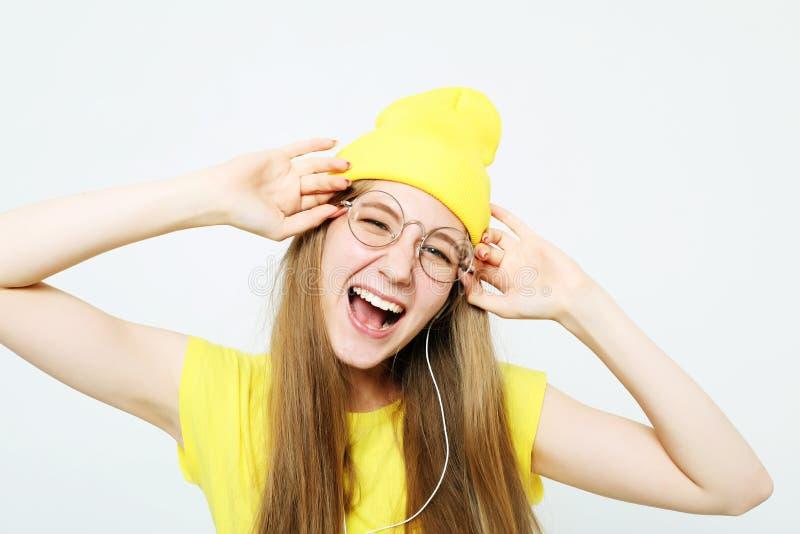 Forme a la muchacha bastante fresca en auriculares que escucha la música que lleva el sombrero y la camiseta amarillos sobre el f fotografía de archivo