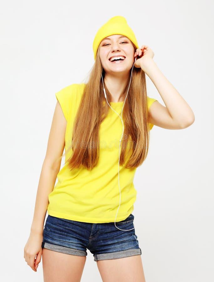 Forme a la muchacha bastante fresca en auriculares que escucha la m?sica que lleva el sombrero y la camiseta amarillos sobre el f fotos de archivo