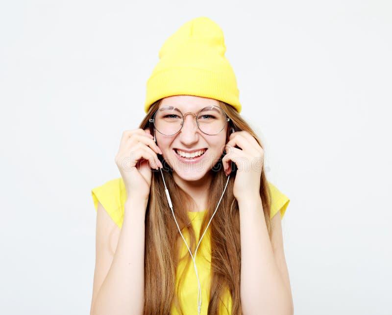 Forme a la muchacha bastante fresca en auriculares que escucha la m?sica que lleva el sombrero y la camiseta amarillos sobre el f fotografía de archivo