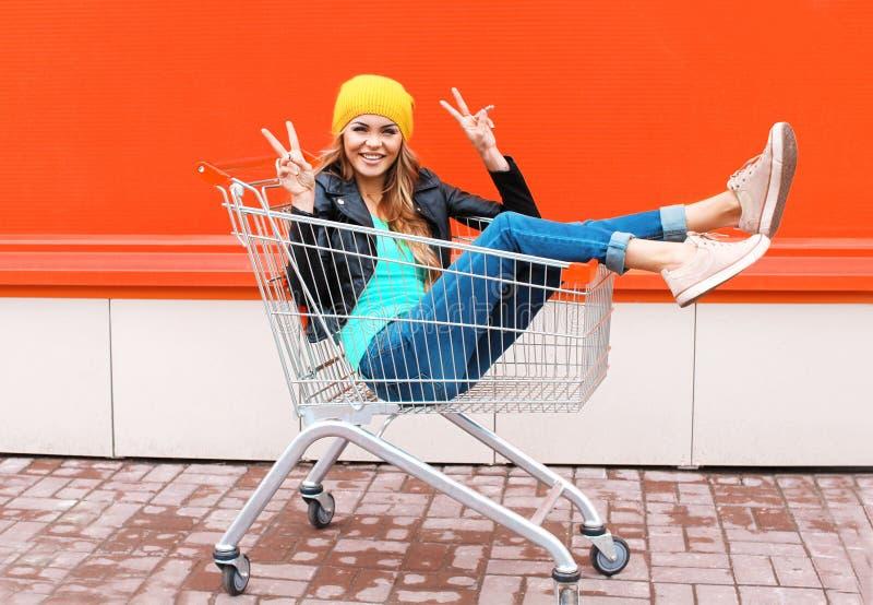 Forme a la muchacha bastante fresca en el carro de la carretilla que se divierte que lleva el sombrero negro de la chaqueta sobre foto de archivo
