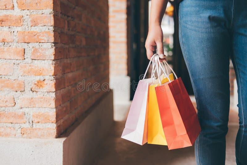 Forme a la muchacha de compras, mujer joven que lleva los panieres coloridos mientras que camina a lo largo de la alameda de comp imagenes de archivo