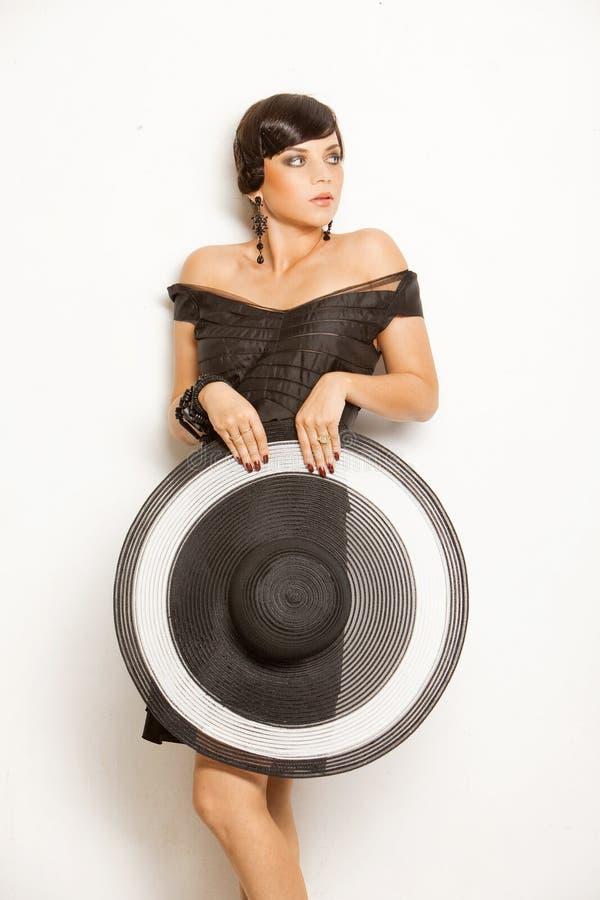 Forme a la muchacha en un sombrero grande en el estudio imagenes de archivo