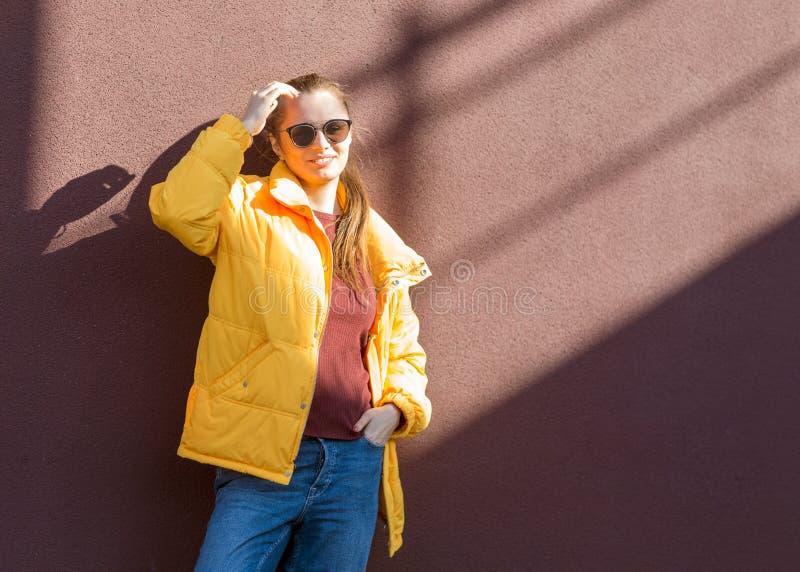 Forme a la muchacha en una presentación amarilla cerca de una pared de la lila imagen de archivo